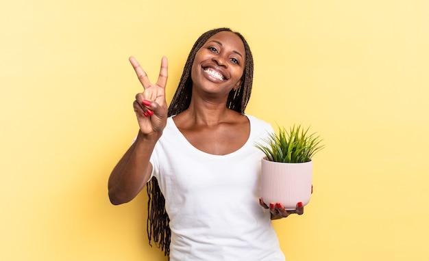 Glimlachend en gelukkig, zorgeloos en positief kijkend, gebarend naar overwinning of vrede met één hand die een plantenpot vasthoudt