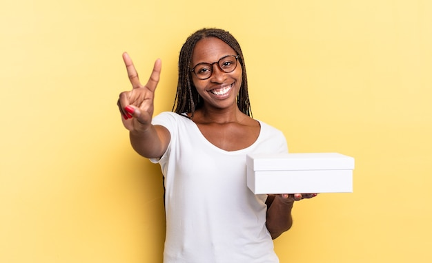 Glimlachend en gelukkig, zorgeloos en positief kijkend, gebarend naar overwinning of vrede met één hand en een lege doos vasthoudend