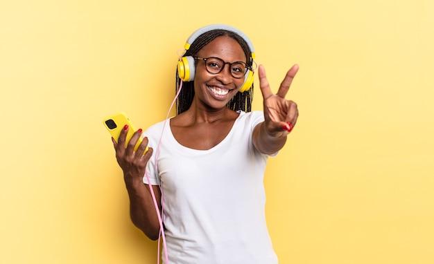 Glimlachend en gelukkig, zorgeloos en positief kijkend, gebarend naar overwinning of vrede met één hand en luisterend naar muziek
