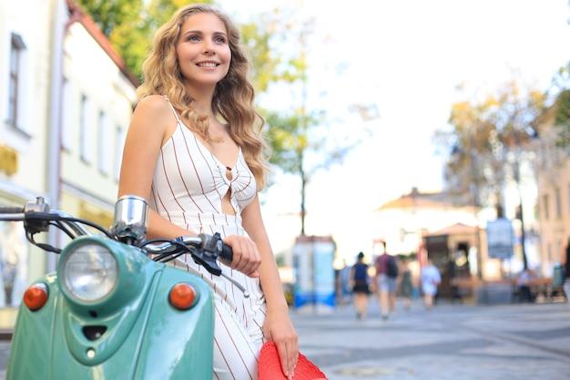 Glimlachend en schattig blond meisje poseren op scooter.
