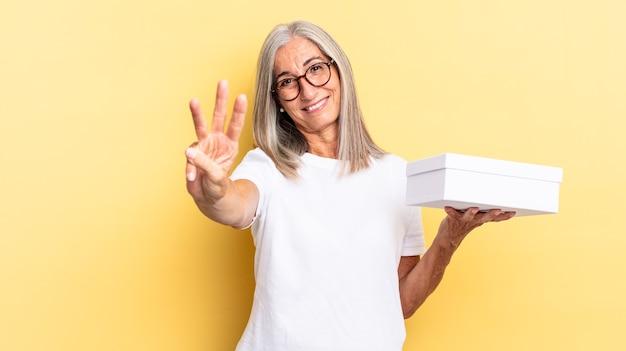 Glimlachend en vriendelijk kijkend, nummer drie of derde tonend met de hand naar voren, aftellend en een witte doos vasthoudend