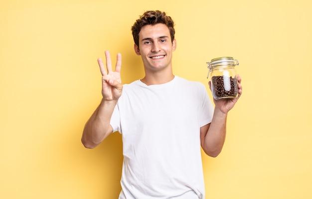Glimlachend en vriendelijk kijkend, nummer drie of derde tonend met de hand naar voren, aftellend. koffiebonen concept