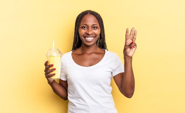 Glimlachend en vriendelijk kijkend, nummer drie of derde tonend met de hand naar voren, aftellend. milkshake concept