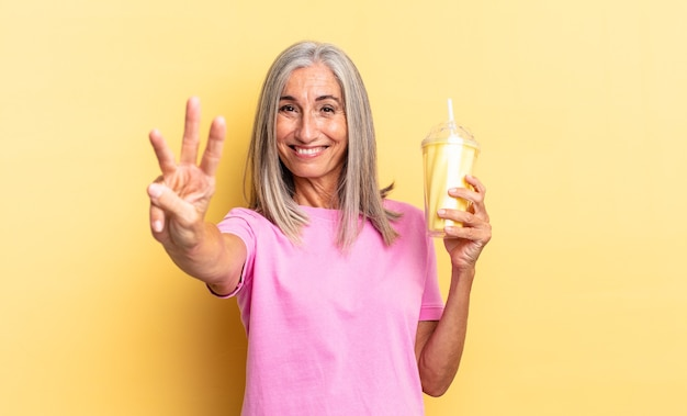 Glimlachend en vriendelijk kijkend, nummer drie of derde tonend met hand naar voren, aftellend en een milkshake vasthoudend