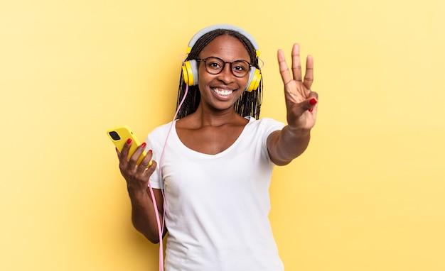 Glimlachend en vriendelijk kijkend, nummer drie of derde tonend met hand naar voren, aftellend en muziek luisterend
