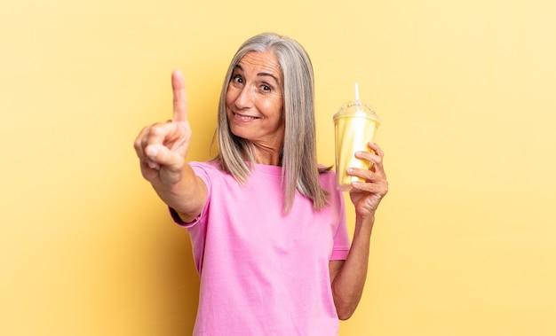 Glimlachend en vriendelijk kijkend, nummer één tonend of eerste met hand naar voren, aftellend en een milkshake vasthoudend