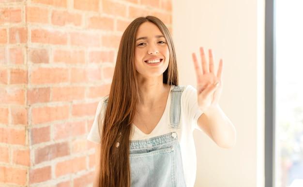 Glimlachend en vriendelijk kijkend, nummer vier of vierde met de hand naar voren, aftellend