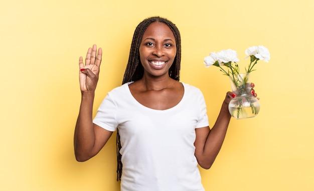 Glimlachend en vriendelijk kijkend, nummer vier of vierde tonend met de hand naar voren, aftellend. decoratief bloemenconcept