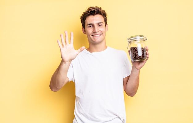 Glimlachend en vriendelijk kijkend, nummer vijf of vijfde tonend met de hand naar voren, aftellend. koffiebonen concept