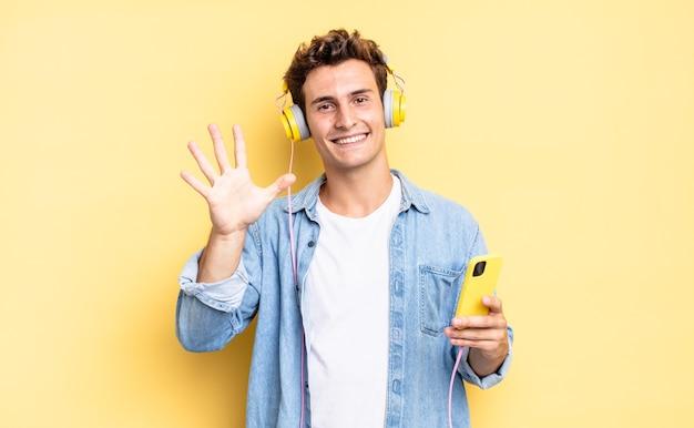 Glimlachend en vriendelijk kijkend, nummer vijf of vijfde tonend met de hand naar voren, aftellend. koptelefoon en smartphone concept