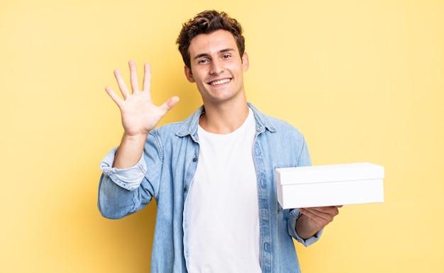 Glimlachend en vriendelijk kijkend, nummer vijf of vijfde tonend met de hand naar voren, aftellend. witte doos concept