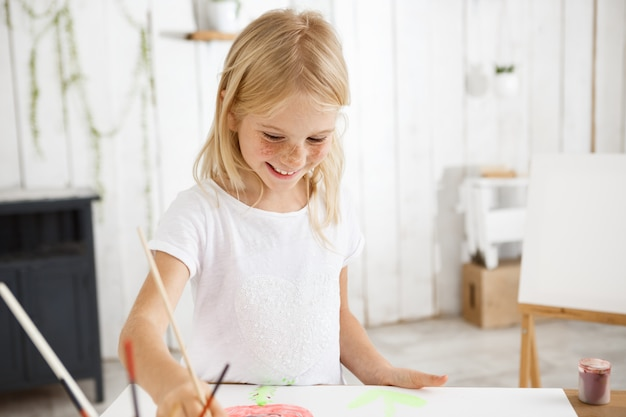 Glimlachend en vrolijk, vol vreugde kind met blond haar en sproeten met penseel in haar hand en ambitieus schilderij in de kunstkamer.
