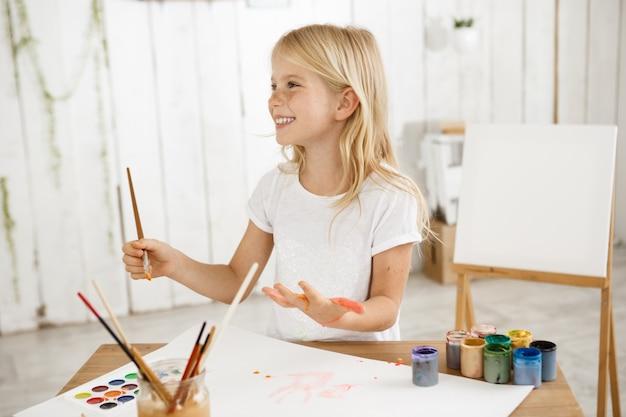 Glimlachend engelachtig mooi kind met blond haar, gekleed in een wit t-shirt schilderij op haar handpalm.