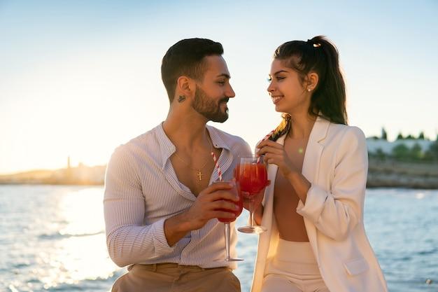 Glimlachend etnisch paar cocktails drinken aan de kade
