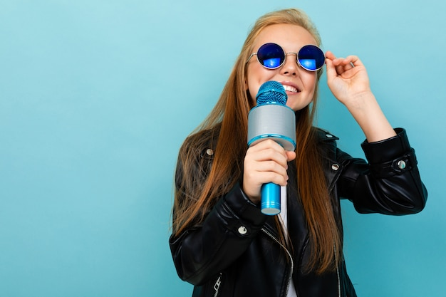 Glimlachend europees meisje dat in zonnebril met een microfoon op lichtblauw zingt