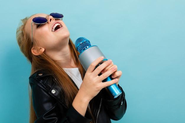 Glimlachend europees meisje in een leerjasje in zonnebril die met een microfoon op lichtblauwe muur zingen