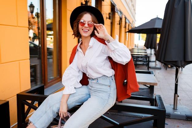 Glimlachend europees meisje in schattige oranje zonnebril, jas en zwarte hoed zitten buiten.