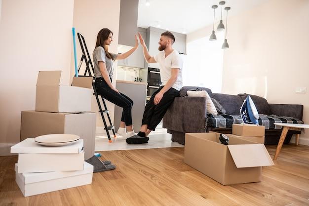 Glimlachend europees paar meisje en man geven elkaar vijf thuis. concept van verhuizen in nieuwe flat. idee van jong gezin. kartonnen dozen met dingen. interieur van studio-appartement. zonnige dag
