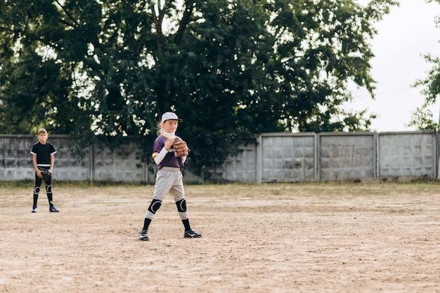 Glimlachend, gefocust meisje in een honkbal uniform bereidt zich voor op het spel. honkbaltraining