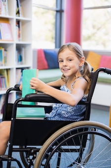 Glimlachend gehandicapt schoolmeisje die op rolstoel boeken in bibliotheek houden