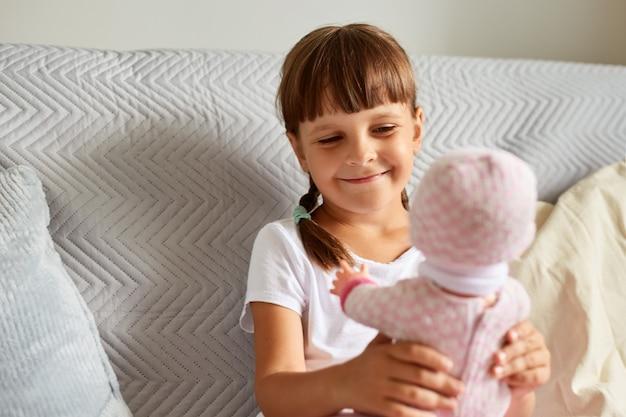 Glimlachend gelukkig charmant kind met donker haar en staartjes met een pop in haar hand, kijkend naar speelgoed met een glimlach, kind met een wit casual t-shirt dat binnen speelt.