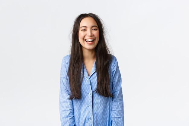Glimlachend gelukkig en energiek aziatisch meisje met slordig haar dat pyjama's draagt
