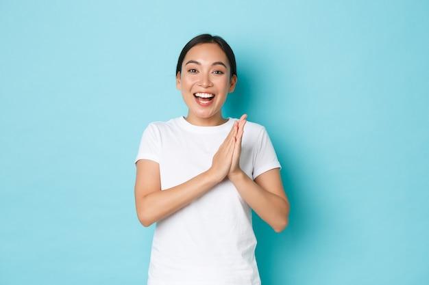 Glimlachend, gelukkig en opgetogen aziatisch meisje dat zich verheugt over iemands prestatie, in de handen klappen verbaasd en persoon feliciteren met overwinning of overwinning, tevreden kijkend over blauwe achtergrond