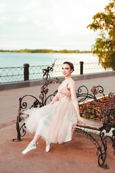 Glimlachend gelukkig in een roze zijden jurk zit op een smeedijzeren bankje in een park aan de oever van de rivier bij zonsondergang...