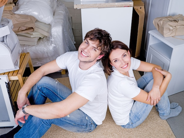 Glimlachend gelukkig jong koppel rug aan rug zitten na het verplaatsen - hoge hoek