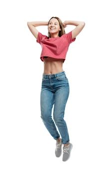 Glimlachend gelukkig jong meisje in jeans die emotioneel terwijl het houden van handen achter haar hoofd springen. geïsoleerd op een witte muur. volledige hoogte. verticaal.