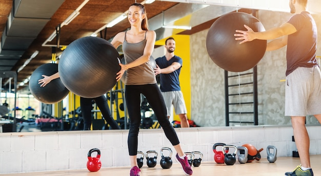 Glimlachend gelukkig kaukasisch paar in sportkleding die pilatesoefeningen in gymnastiek doen.