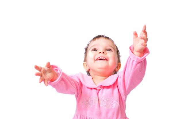 Glimlachend gelukkig klein meisje van de éénjarige baby in roze kledingszitting met omhoog handen.