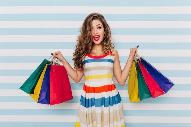 Glimlachend gelukkig meisje dat in lichte kleding nieuwe kleren koopt. portret van prachtige dame met plezier.