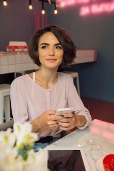 Glimlachend gelukkig meisje dat mobiele telefoon houdt
