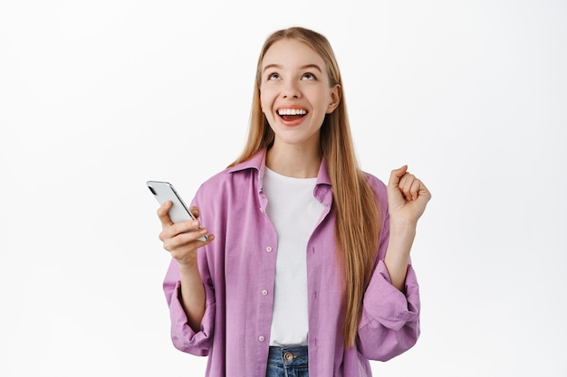 Glimlachend gelukkig meisje dat opgelucht opkijkt na het winnen op de mobiele telefoon, smartphone vast te houden en zich te verheugen, prestatie in app te vieren, staande over witte muur.