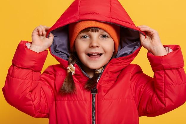 Glimlachend gelukkig meisje dat rood jasje en oranje glb draagt