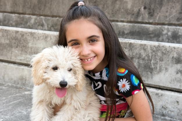 Glimlachend gelukkig meisje met haar huisdierenpoedel