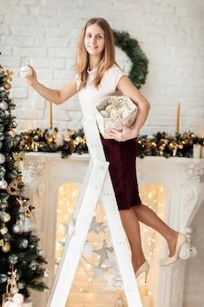 Glimlachend gelukkig meisje versiert de kerstboom op de witte bakstenen muur achtergrond in de studio.