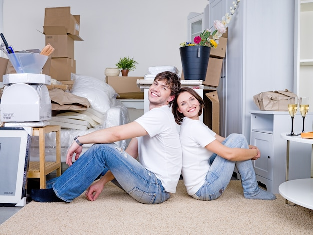 Glimlachend gelukkig paar dat rug aan rug op de vloer in het nieuwe huis zit