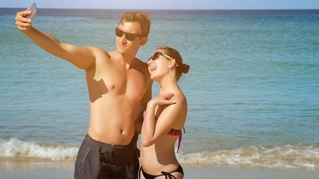 Glimlachend gelukkig paar in zwemkleding en zonnebril maakt selfie met smartphone op zonnig strand zonlicht