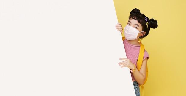 Glimlachend gelukkig schattig aziatisch kind dat masker draagt om haar te beschermen tegen het virus covid-19 dat zich verschuilt achter een leeg wit bord dat op gele muur wordt geïsoleerd.