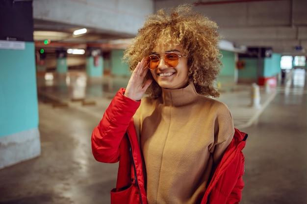 Glimlachend gemengd ras hip hop meisje in jas permanent in garage en zonnebril aan te passen.