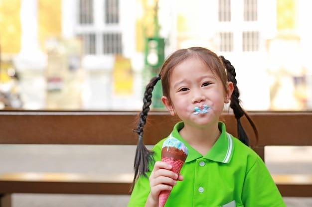Glimlachend geniet weinig aziatisch jong geitjemeisje van het eten van roomijskegel met vlekken rond haar mond.
