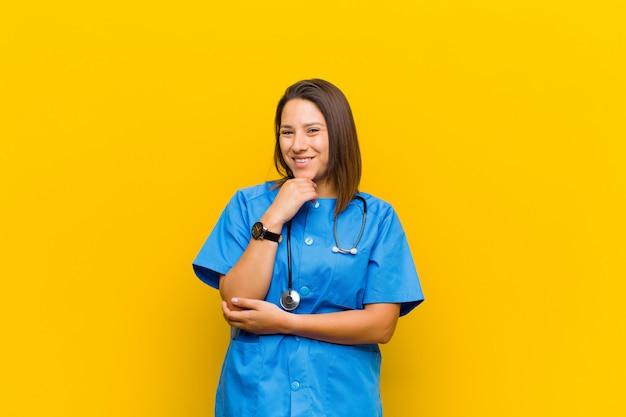 Glimlachend, genietend van het leven, gelukkig, vriendelijk, tevreden en zorgeloos met hand op kin geïsoleerd tegen gele muur