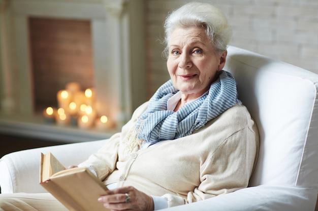 Glimlachend gepensioneerd vrouw leesboek