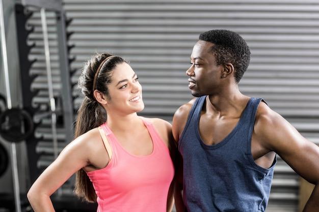Glimlachend geschikt paar die bij gymnastiek omhelzen