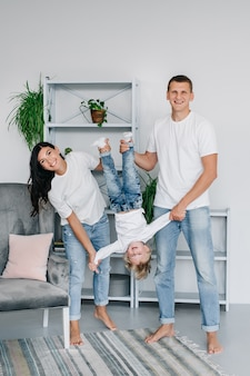Glimlachend gezin plezier full body, in een gezellig stijlvol interieur houdt hun zoon ondersteboven.