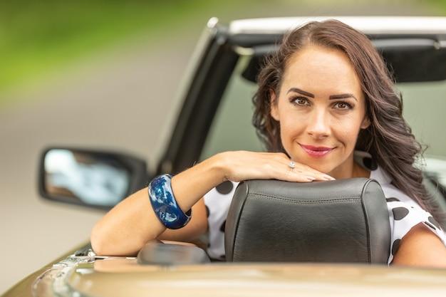 Glimlachend goed uitziende vrouwelijke chauffeur zit in een cabriolet, achteruit gedraaid.
