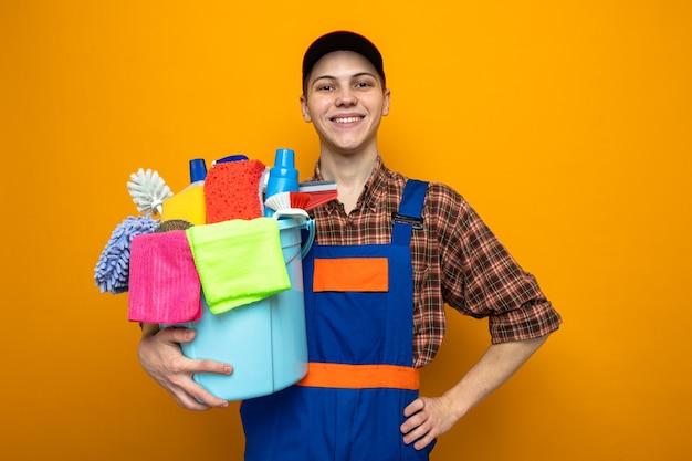 Glimlachend hand op een hippe jonge schoonmaakster met uniform en pet met emmer schoonmaakgereedschap