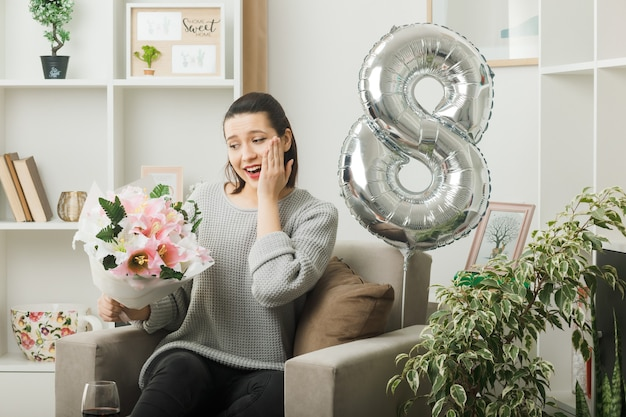 Glimlachend hand op wang mooi meisje op gelukkige vrouwendag met boeket zittend op fauteuil in woonkamer